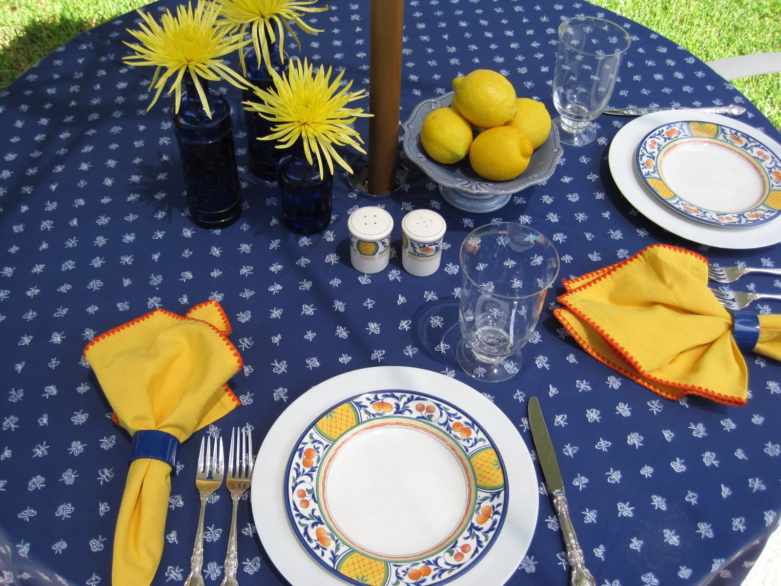 I Used The Same Tablecloth, Dinner Plates, Silver, And Glasses, But Added  Yellow Spider Mums To The Cobalt Blue Bottles And Lemons To The Blue Footed  Dish.