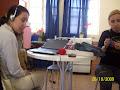 Perla usando os fones para ouvir o laptop e a Bruna sentada ao lado.