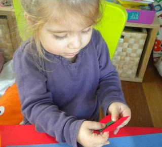 toddler gluing hand made Christmas ornament