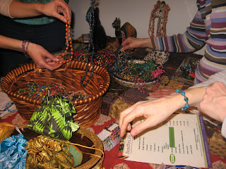 Lots of hands dipping into a bounty of beads.