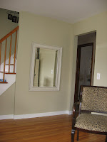 After: serene green walls, white ceiling and trim, and a sleek off-white mirror
