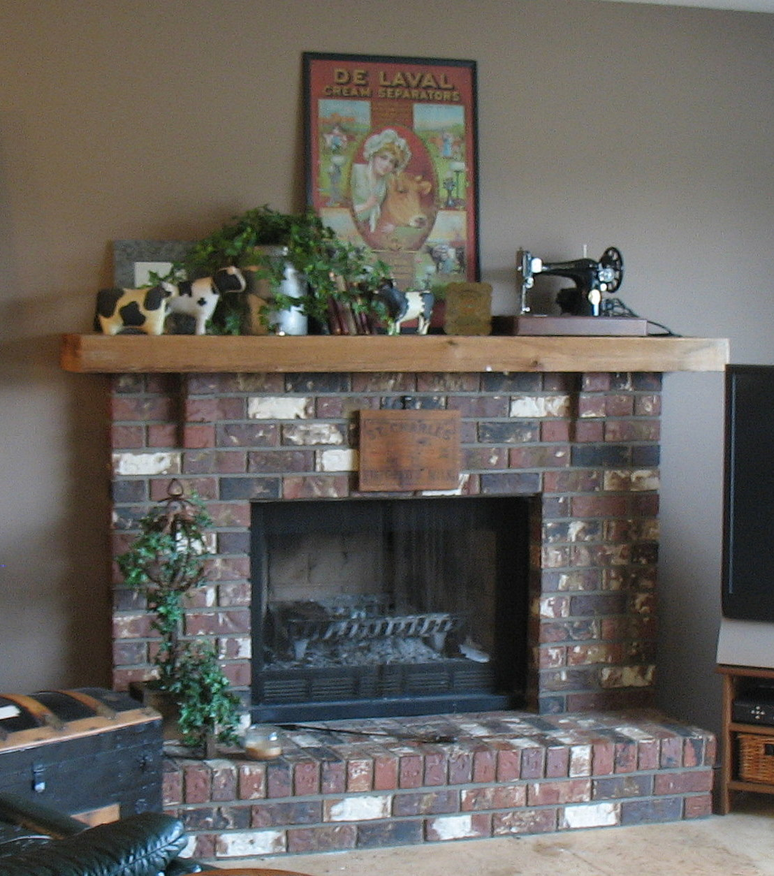 Small Inside Room Fireplace Decorated With Painting And Plants That