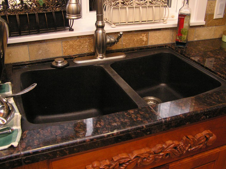 commercial photo of kitchen with granite and granite sink