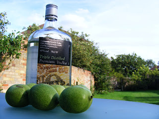 A bottle of vodka and several green, unripe walnuts on a table in a garden