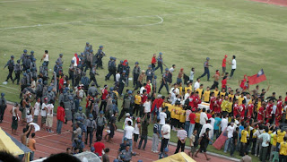 >Burmese football game goers under the pointing guns of riot police