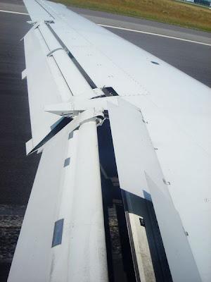 Un avión aterrizando con flaps y spoilers desplegados