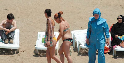 conservative Muslim woman wears a hasema, a shroud-like swimsuit, on ...