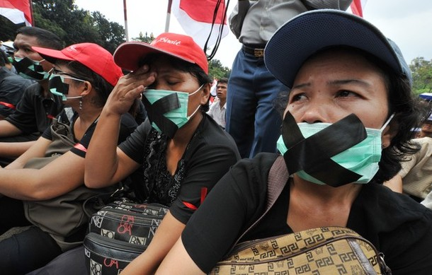 Indonesian Christians cover their mouths during a protest against    Indonesian Christians
