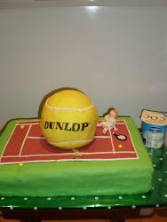 tarta de pelota dunlop de tenis, encima de la pista de tenis.