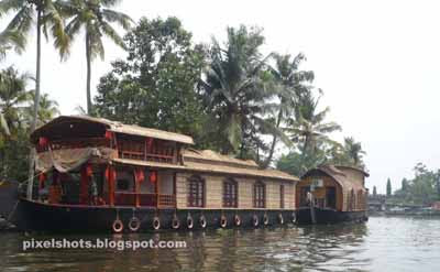docked houseboats in kumarakom lake, boat journey through vembanadu lake, backwater tourist spots in kerala, kumarakom houseboats and boat journey, kerala houseboats, vembanadu tourism, tourist spots in kottayam