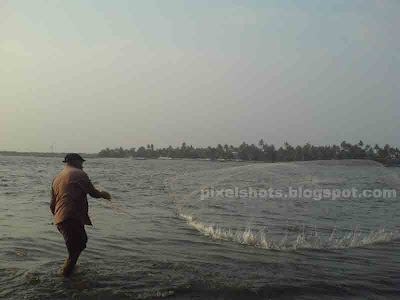 kerala fisherman,beach fishing photos,throwing fish net,fisherman throwing net in the beach of fort cochin kerala,casting fish net