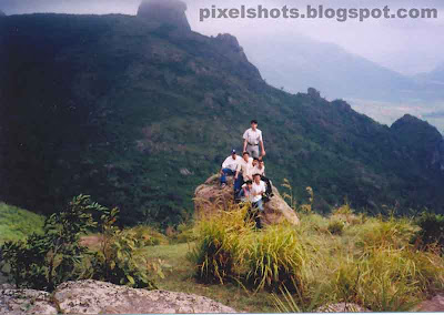 tour-trip-to-ramakkalmedu,kerala-hillstation-tour-snaps,tour trip group photograph,college-tour-to-ramakkalmedu,friends standing over a rock in a scenic place in ramakkalmedu mountains