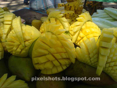photographs of mangoes sliced in designs from street side fruits sellers in kerala india,sliced fruits in streets, street fruit merchants, fruits sold in pulling carts, unthu vandy pazha kachavadam, kerala mangoes, mango fruit uses and medicinal value, closeup fruits photography