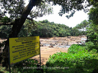 yellow caution board seen aside kallada river near thenmala ottakkal lookout,caution board of water authority saying danger zone of river,dont enter river,dangerous rivers of kerala,yellow danger caution board of kerala water authority