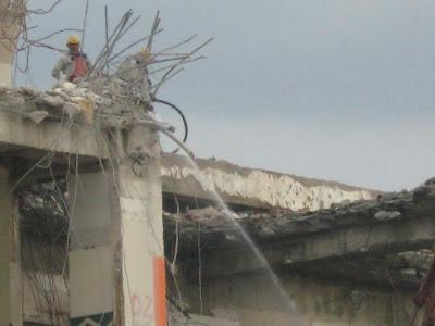 Worker spray water to control dust during Jaya Supermarket demolishing