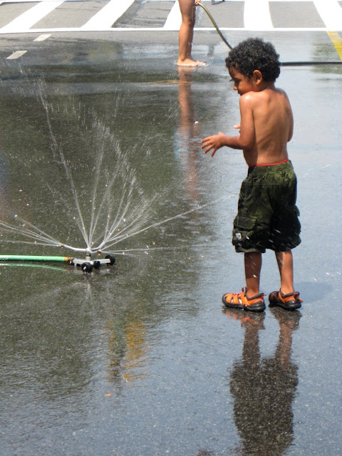 Boy on street playing with sprinkler