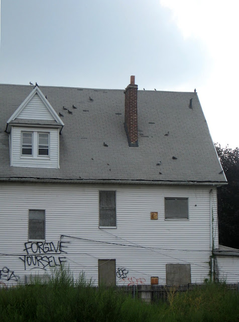 Old house with graffiti with the words forgive yourself on it