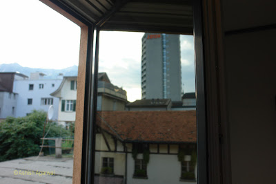 Photo of view of Interlaken through a reflection in a glass window