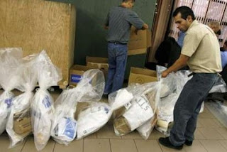 A worker places packages of ballots at the Supreme Court of Elections building that was being used to count Sunday's votes on a referendum to decide whether to approve the country's participation in the Central American Free Trade Agreement (CAFTA) with the U.S, in San Jose, October 9, 2007. The Bush administration on Monday welcomed Costa Rica's narrow approval of a free trade agreement with the United States, after a national debate that split the tiny Central American democracy. REUTERS/Juan Carlos Ulate (COSTA RICA)