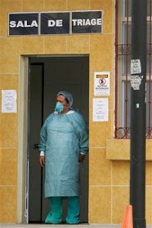 A doctor, wearing protective clothing and mask as a precaution against swine flu, stands outside an trauma area set up to treat cases of suspected swine flu at a hospital in San Jose, Monday, May 11, 2009. (AP Photo/Kent Gilbert)