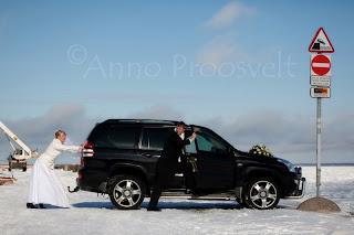 Pruut ja peigmees lükkavad pulmaautot merre. Tallinna Lennusadam.