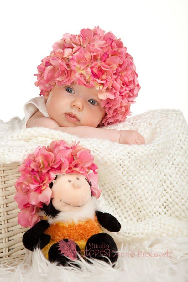 Pisike beebitüdruk roosa lillemütsiga Fotopesa fotostuudios