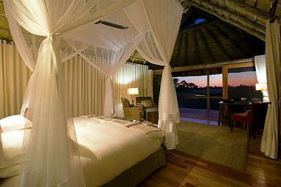 fancy African safari lodge bedroom white gauze curtains bed canopy African view