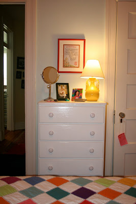 white dresser with yellow lamp