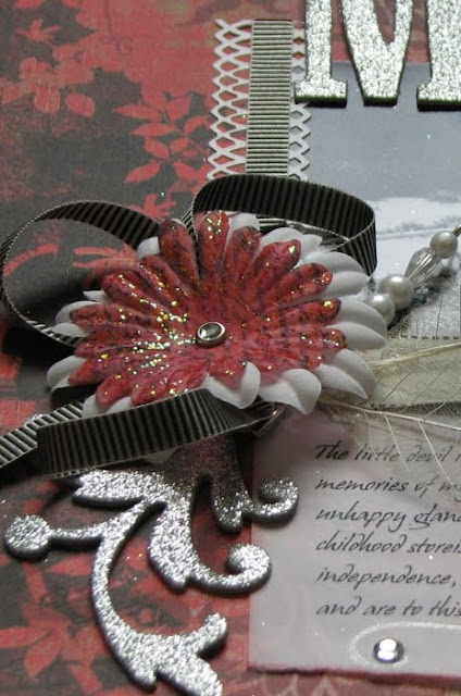 Closeup of the main embellishment with layered flowers, chipboard swirl, Pretties Pin and loops of ribbon