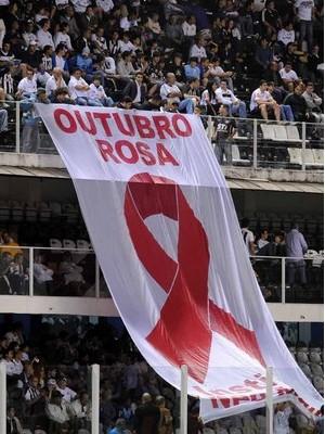 Bandeira com o laço símblo do Outubro Rosa estendida na arquibancada