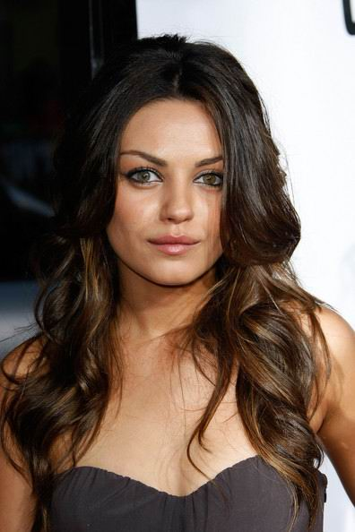 Mila Kunis has a beautiful long wavy hairstyle.