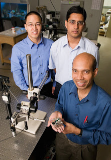 Taher Saif, a professor of mechanical science and engineering, holds a piezo actuated stage for nanoscale material studies in scanning electron microscopes. Graduate students Jong Han, left, and Jagannathan Rajagopalan explored aluminum films and gold films. Photo by L. Brian Stauffer