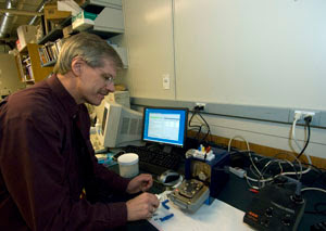 Kevin Moeller's group is pioneering new methods for building libraries of small molecules on addressable electrode arrays. This is done so that the molecules can be monitored for their behavior in real-time and in turn used to probe the binding requirements of drug receptor sites. Here, Professor Moeller is pictured loading a chip containing an electrode array into an electrochemical analyzer. David Kilper/WUSTL Photo