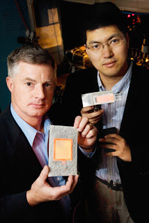 Gary Eden, professor and director of the Laboratory for Optical Physics and Engineering, left, with Sung-Jin Park, visiting professor and research scientist in electrical and computer engineering, hold flat-panel lamps made with aluminum foil and tiny plasma arrays their team developed. Photo by L. Brian Stauffer