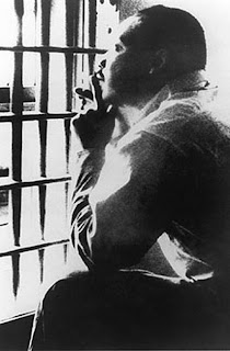 Martin Luther King Jr. looks through the bars of a Burmingham, Alabama, cell in April 1963