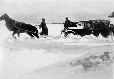 Horses pulling car stuck in snow