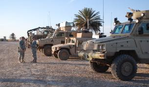 A row of armored vehicles — RG-31s, a Humvee and a Buffalo — are ready to leave on patrol.