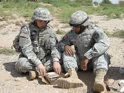 Two Soldiers look at the components of the First Strike Ration during a recent evaluation at Fort Bliss, Texas.