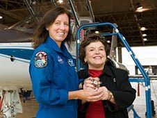 Joan Kerwin, director of The Ninety-Nines, joins astronaut Shannon Walker as the two display a special item to onlookers in an Ellington Field hangar on Oct. 22