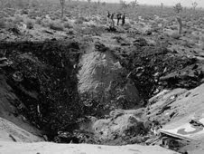 Investigators pore over the site of the nose-first, high-impact JF-104A crash that left this large crater in the desert near Edwards Air Force Base in December 1962. NASA test pilot Milton O