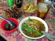 A selection of Indonesian food, including Soto Ayam (chicken soup), sate kerang (shellfish kebabs), telor pindang (preserved eggs), perkedel (fritter), and es teh manis (sweet iced tea)