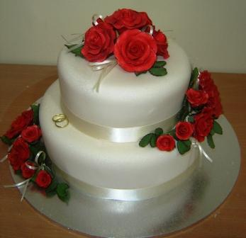 round two tiered wedding cake with red lace and topped with red roses