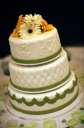 Delicate quilted three tier wedding cake with orange and white gerbera