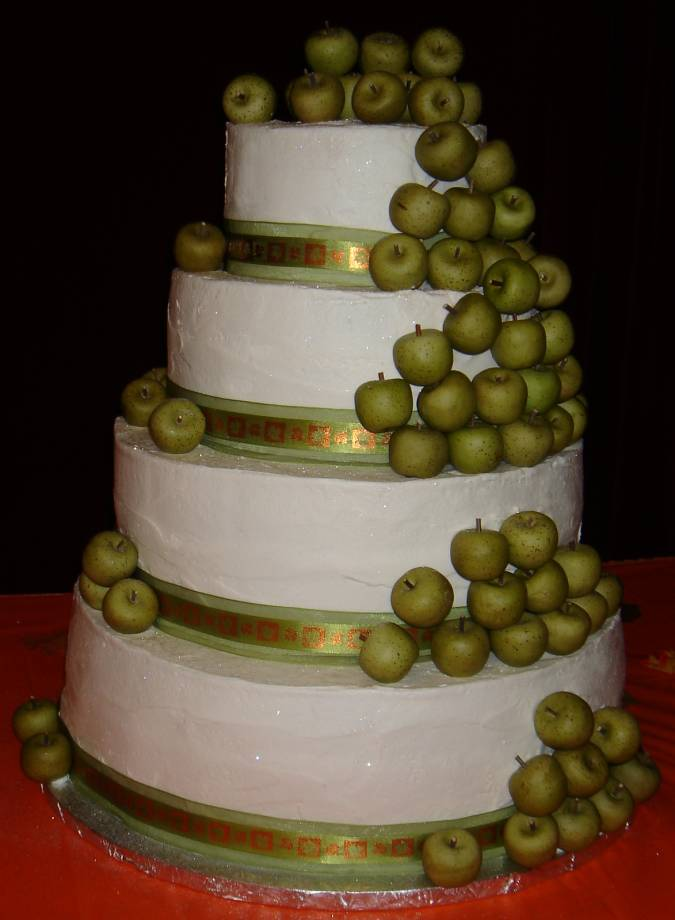 Unique four tier wedding cake with green apples cascading down the cake