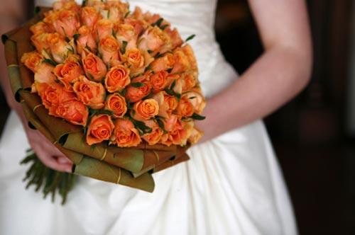 A bridal bouquet made up of beautiful orange roses can signify the burning
