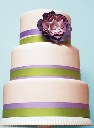 Three tier white wedding cake with lilac flowers and lime green roses