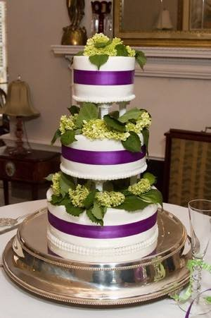 Three tier white wedding cake separated by columns with wide purple satin