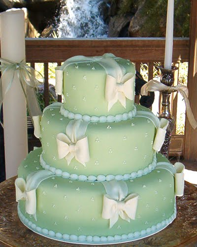 Three tier pastel green icing wedding cake with cute white bows