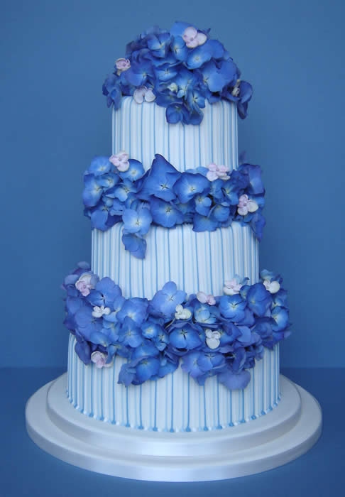 Stripy three tier white wedding cake with blue hydrangeas