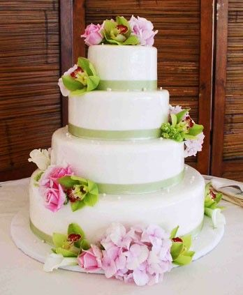 Four tier white round wedding cake with green trimming green orchids and